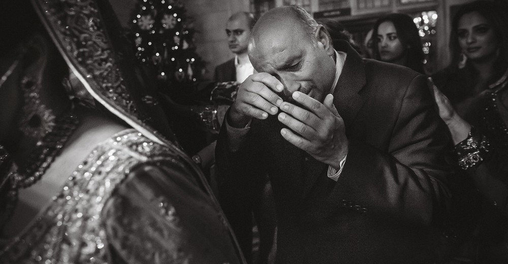 A father sheds a few tears at a asian wedding, as he is overwhelmed just as his daughter is leaving to start her married life.